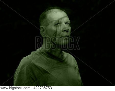 Creepy Green Man Portrait With Shadow On Face. Scary Look Of Mature Senior Man In Nature. Madness, H