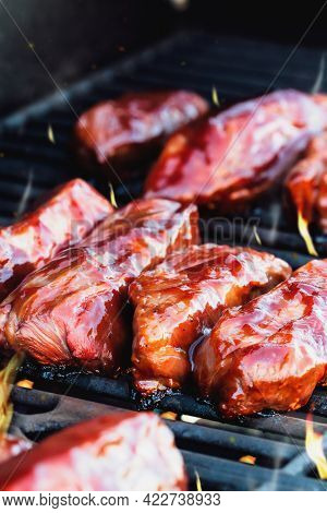 Vertical Shot Of Boneless Beef Ribs Grilling Over Flames With Tangy Barbecue Sauce For A Summer Cook