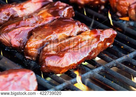 Boneless Beef Ribs Grilling Over Flames With Tangy Barbecue Sauce For A Summer Cook Out. Extreme Sha