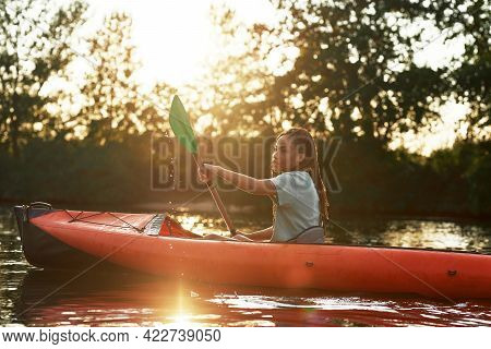 Attractive Young Woman Holding A Paddle While Kayaking In A Lake Surrounded By Nature On A Late Summ