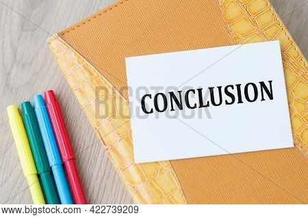 Notepad And White Card With Text Conclusion In The Wooden Background Next To Colored Markers