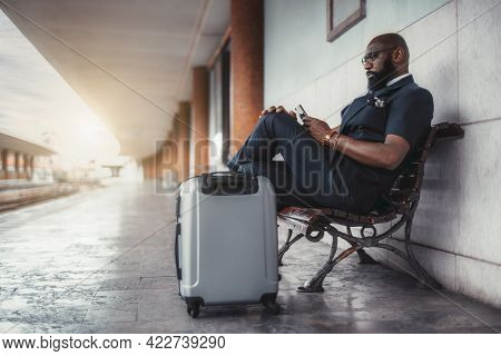 A Serious Black Man Entrepreneur On The Railroad Platform With His Bags Is Phoning While Waiting For