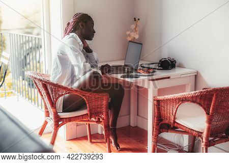 View Of A Sensual Young African Woman With Braids, Using Her Laptop While Sitting On A Cane-chair Ha