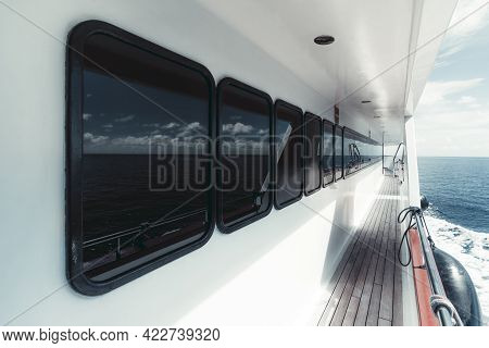 Wide-angle View Of The Side-deck Of A Luxurious White Safari Yacht With A Row Of Windows Of The Deck
