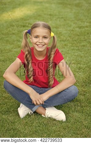Little Girl Cute Ponytails Hairstyle Relaxing On Green Grass, Optimistic Concept