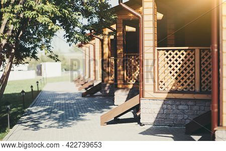An Alleyway With Trees And Low Lanterns On The Left And The Row Of Equal Wooden Summer Verandas With