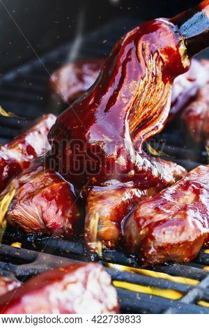 Vertical Shot Of Boneless Beef Ribs Grilling Over Flames With Barbecue Sauce Added With Bbq Mop. Ext