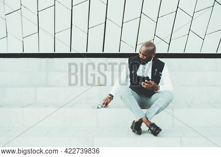 A Fancy Adult Bald African Guy In An Elegant Outfit With A Waistcoat Is Sitting On A Marble Step Out