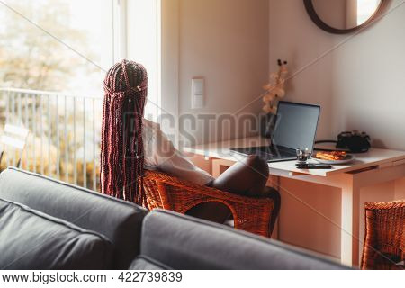 View From Behind Of A Black Woman With Long Hanging Braids Sitting In The Living Room Of Her House I