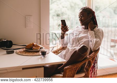 Portrait Of A Sexy Young African Female Sitting On A Wicker Chair In The Kitchen Next To The Balcony