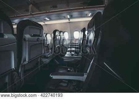 A Dark Interiorof An Aircraft: The Row Of Modern Empty Thin Leather Seats With Armrests Down, Shall