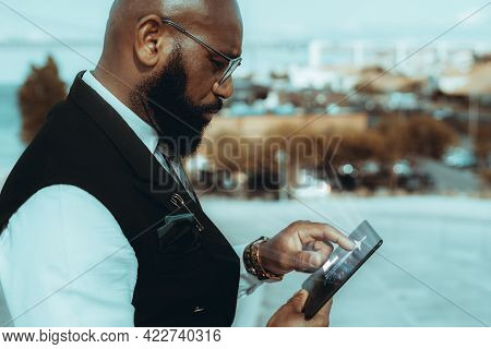A Side View Of An Elegant Mature Bald Black Guy Entrepreneur Outdoors In Eyeglasses And Fashionable