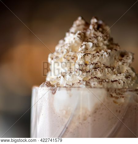 Airy Foam On Milkshake Cocktail Sprinkled With Grated Chocolate. Close Up Of Puffy Whipped Cream Des