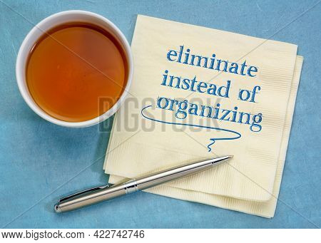 eliminate instead of organizing - handwriting on a napkin with a cup of tea, simplicity and decluttering concept