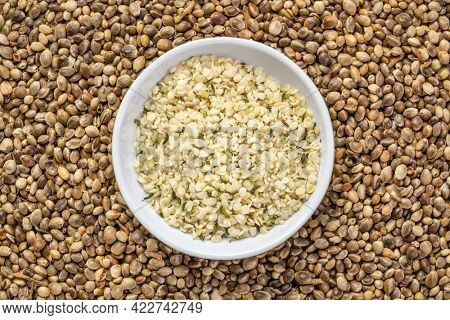 hemp seed hearts in a small ceramic bowl against a background of dry seeds, superfood and healthy eating