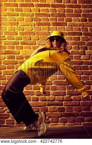 Cool street dancer girl in bright trendy clothes and sunglasses dancing by a brick wall background. Hip-hop dancer.