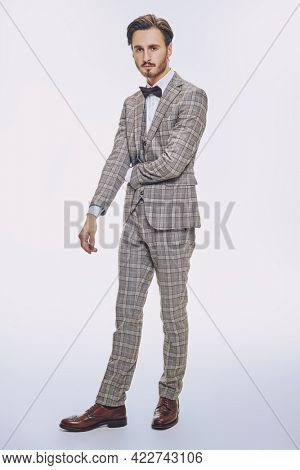 Full length portrait of a good looking handsome brunet man wearing elegant classic suit and a bow-tie on a white background. Men's beauty, fashion.