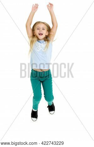Happy Girl Jumping With Raised Hands. A Cute Girl In A T-shirt And Jeans Has Fun On A White Backgrou