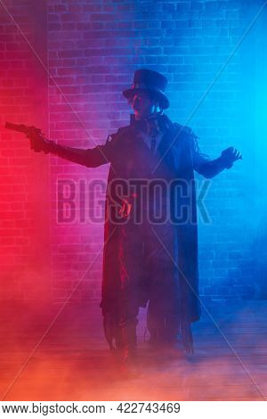 Courageous steampunk male warrior with a gun on a foggy street. World of steampunk.