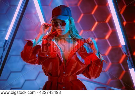 Stylish sexy woman in trendy red jacket, baseball cap and red glasses posing in the light of neon lamps. Techno style, disco. Fashion shot.