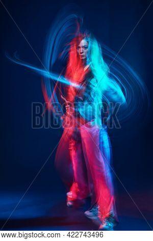 Modern style dances. Professional hip hop dancer girl dancing at studio in neon light.