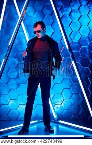Handsome man in black sunglasses and black leather jacket posing among the neon lamps. Men's style and fashion. Futurism, techno style.