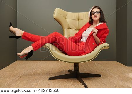 Full length portrait of a beautiful business lady sitting in a chair in Art Nouveau style. Business, elegant businesswoman. Interior, furniture.