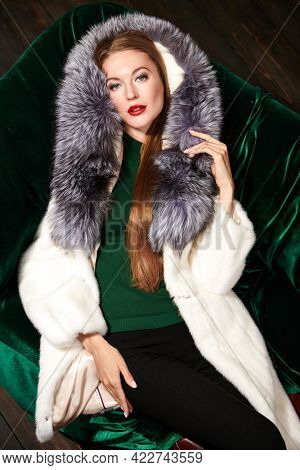 Beautiful young woman in an expensive mink and silver fox fur coat lying on a velvet sofa. Fur coat fashion. Luxury lifestyle.