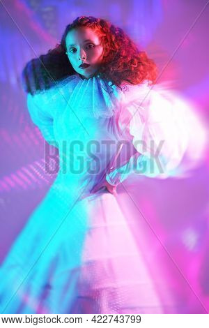Historical style in vogue. Sophisticated female model with lush red curly hair posing in a stylized white dress with late renaissance ruffled collar. Studio portrait in mixed colored light.