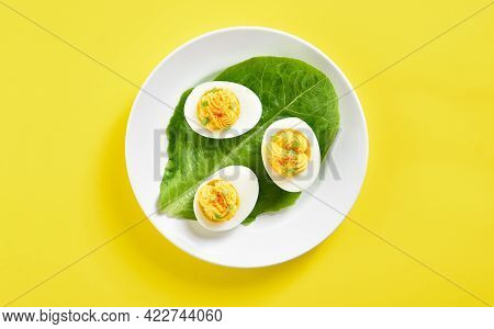 Close Up View Of Deviled Eggs With Paprika, Mustard And Mayonnaise Over Yellow Background. Top View,