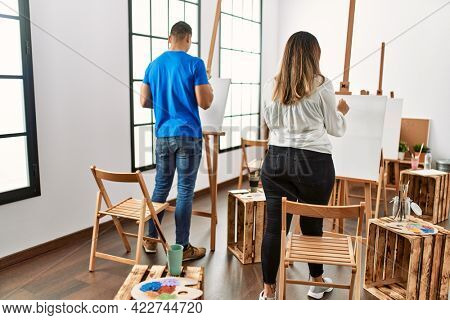 Two students on back view painting at art school.