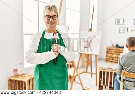 Two senior paint student smiling happy painting at art studio. Woman standing with smile on face holding paintbrushes.