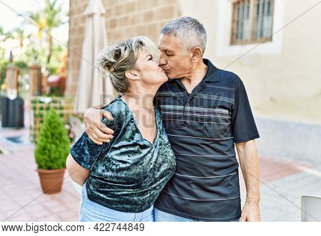 Middle age caucasian couple of husband and wife together on a sunny day outdoors. Smiling happy in love hugging at the city.