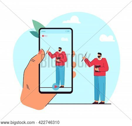 Hand With Phone Making Online Recording Of Male Teacher. Man Standing, Holding Clipboard And Pointer