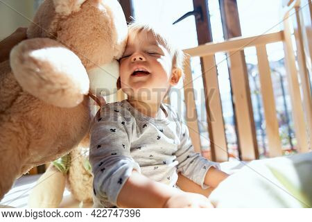 Smiling Little Child Sitting On A Wooden Bed Leaning Against A Large Teddy Bear