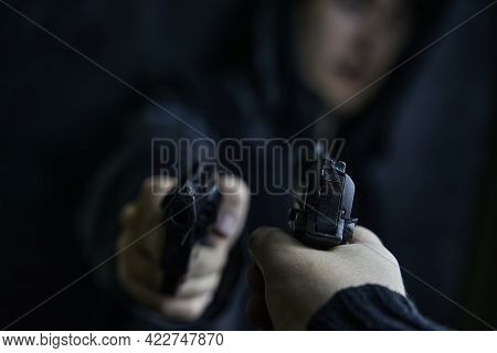 Two Shooters Threaten Each Other With Weapons. First-person View Of Hand With Pistol Pointed At Guy