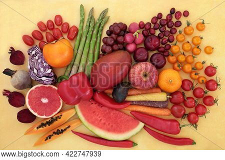 Healthy fruits and vegetables high in lycopene for an immune system boost with super foods also high in anthocyanins, antioxidants, vitamins, minerals and dietary fibre.  On mottled yellow background.