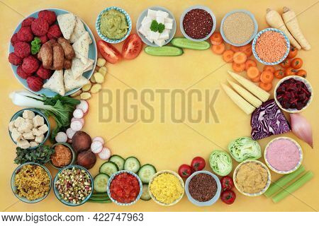 Vegan food for immune system boosting diet high in antioxidants, anthocyanins, fibre, minerals, vitamins, protein and omega 3. Plant based health food for ethical eating. On mottled yellow.