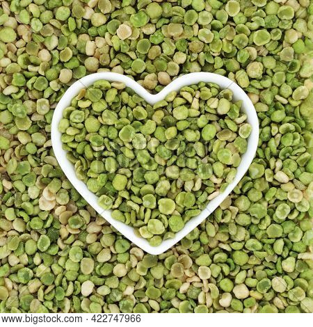 Roasted green peas healthy food in a heart shaped dish and forming a background. High in dietary fibre, protein, vitamins and minerals and has heart health benefits. Flat lay, top view.