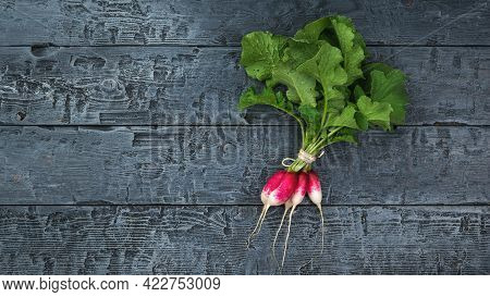 Top View Of A Bunch Of Fresh Radishes On A Black Wooden Table. A Fresh Crop Of Radishes.