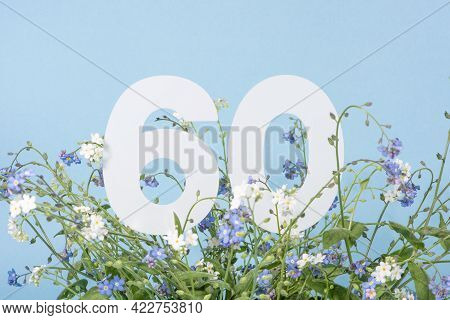 Number Sixty Among Blue Forget-me-not Flowers.  Birthday, Anniversary, Jubilee Concept. For Invitati