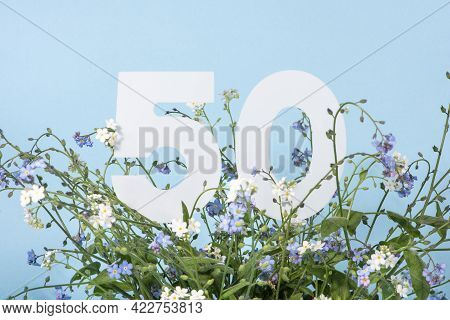 Number Fifty Among Blue Forget-me-not Flowers.  Birthday, Anniversary, Jubilee Concept. For Invitati
