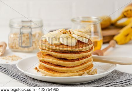 A Stack Of Oatmeal Banana Pancakes With Slices Of Fresh Bananas, Walnuts And Honey On Top With Cup O