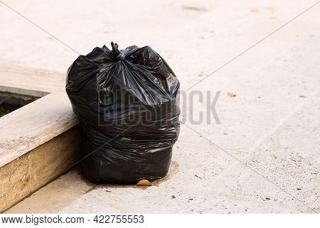 Black Plastic Garbage Bag On The Sidewalk.