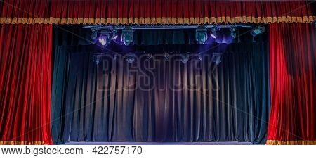 Red Curtain On The Theater Stage, Illuminated By Spotlights. Intermission Between Performances. The