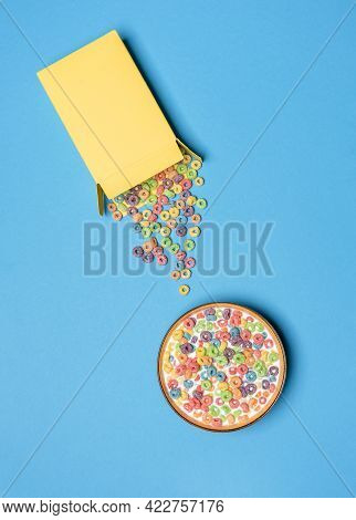 Bowl With Multicolored Cereals And Milk On A Blue Table, Above View. Cereal Box Overturned On A Colo