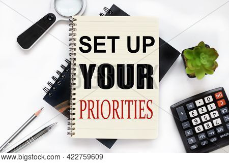 Set Up Your Priorities. An Open Notebook Lies On A Closed Notebook Near A Calculator And A Magnifyin