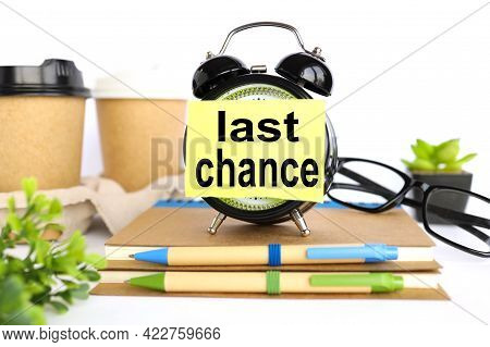 Last Chance. There Is A Sticker On The Alarm Clock. Against The Background Of A Paper Cup With Coffe