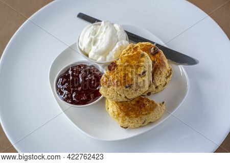 Scones With Jam And Cream On White Plate