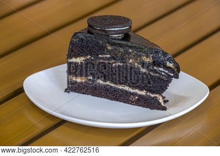 Slice Of Chocolate Cookies Cake On White Plate
